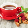 Cup of tea with cookies and raspberries on table close-up — Stock Photo