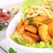 Stock Photo: French fries and home potatoes on plate on board on napkin on wooden table