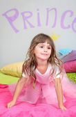 Little girl jumping on bed in room on grey wall background — Stock Photo