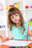 Little girl draws sitting at table in room on shelves background — Stock Photo