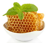 Sweet honeycombs in bowl isolated on white — Stock Photo
