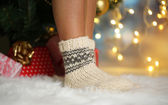 Legs in socks near Christmas tree on carped — Stok fotoğraf
