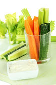 Fresh green celery with vegetables in glass close-up — Stock Photo