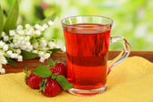 Delicious strawberry tea on table on bright background — Stock Photo
