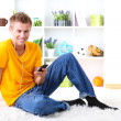 Young man relaxing carpet and listening to music — 图库照片