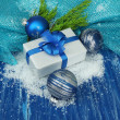 Composition with Christmas balls, gift box and snow on color wooden background — Stok fotoğraf