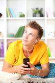 молодой человек расслабляющий ковер и слушать музыку — Стоковое фото