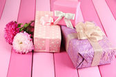 Gifts and flowers, on bright wooden background — Stock Photo