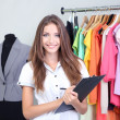 Beautiful young stylist near rack with hangers — Stock Photo #32212853