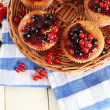 Tasty muffins with berries on white wooden table — Stock Photo #32213225