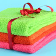 Stock Photo: Towels tied with ribbon on light blue background