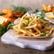 Stock Photo: French fries on tracing paper on board on wooden table