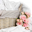 Stock Photo: Rumpled bedding sheets in wicker basket isolated on white