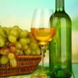 Ripe grapes in wicker basket, bottle and glass of wine, on bright background — Stock Photo #32215903