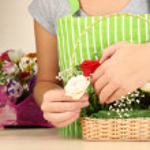 Florist makes flowers bouquet in wicker basket — Stock Photo #32216229