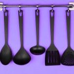 Black kitchen utensils on silver hooks, on purple background — Stock Photo #32216649