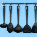 Black kitchen utensils on silver hooks, on blue background — Stock Photo #32216827