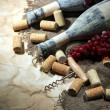 Old bottles of wine, grapes and corks on old paper background — Stock Photo #32217261