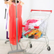 Shopping cart with clothing, on gray wall background — Stock Photo #32217603