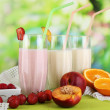 Delicious milk shakes with strawberries and peach on wooden table on natural background — Stock Photo #32217731