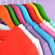 Different shirts on colorful hangers on purple background — Stock Photo #32217817