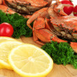 Boiled crabs with lemon slices and tomatoes, on wooden board, close up — Stock Photo #32218027