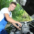 Young car mechanic repairing car engine outdoors — Stock Photo