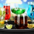 Many glasses of cocktails on tray on table, on bright background — Стоковая фотография