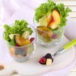 Fruit salad in glasses, on wooden background — Stock fotografie