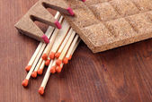 Long matches and dry fuel, on wooden background — Stock Photo