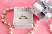 Beautiful box with wedding ring and flower on pink background — Foto Stock