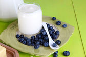 Fresh yogurt with blueberry on wooden table on natural background — Stock Photo
