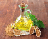 Jar of mustard oil and seeds with mustard flower on wooden background — Foto de Stock
