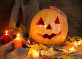 Halloween kürbis und herbstlaub auf hölzernen hintergrund — Stockfoto