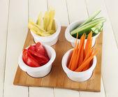 Verduras frescas brillantes cortaron rebanadas en los tazones de fuente en primer plano de la mesa de madera — Foto de Stock
