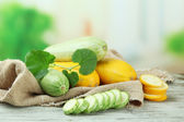 Sliced and whole raw zucchini on wooden table, outdoors — Stock Photo