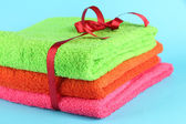 Towels tied with ribbon on light blue background — Stock Photo