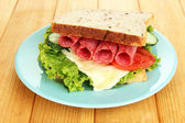Tasty sandwich with salami sausage and vegetables on blue plate, on wooden background — Stock Photo