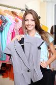 Linda garota escolhe roupa no fundo da sala — Fotografia Stock