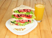 Huge sandwich on wooden table, on wooden background — Stock Photo