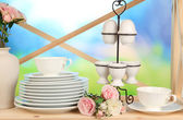 Lots beautiful dishes on wooden shelf on natural background — Stock Photo