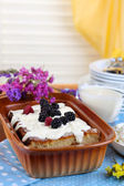 Cheese casserole with raisins in pan on napkin on wooden table close-up — Stock Photo