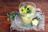 Kopje thee met gember op rouwgewaad op houten tafel — Stockfoto