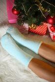 足の上にクリスマス ツリーの近くソックス carped — ストック写真