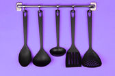 Black kitchen utensils on silver hooks, on purple background — Stock Photo