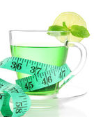 Transparent cup of green tea and measuring tape isolated on white — Stock Photo