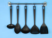 Black kitchen utensils on silver hooks, on blue background — Stock Photo