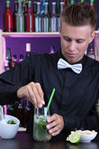 Portrait of handsome barman preparing cocktail, at bar — Stock Photo