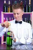 Bartender is pouring champagne into glasses — Stock Photo