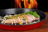 Raw chicken fillets on dripping pan, on fire background — Stock Photo